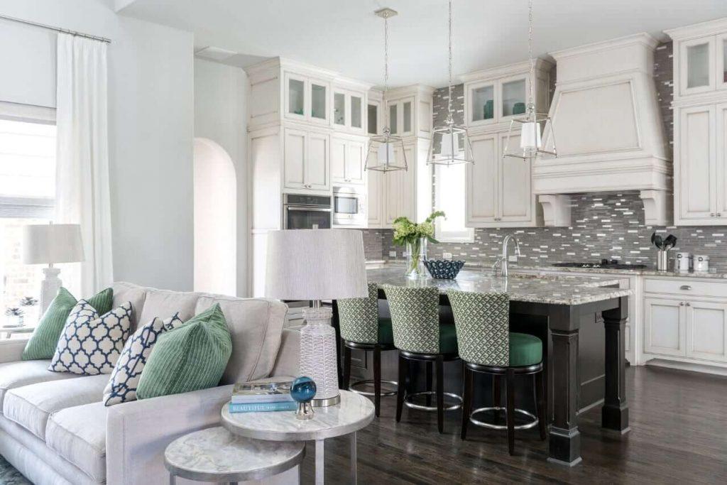 Family room in Dallas TX with gray sofa, green throw pillows, black island, white glaze kitchen cabinets, gray backsplash