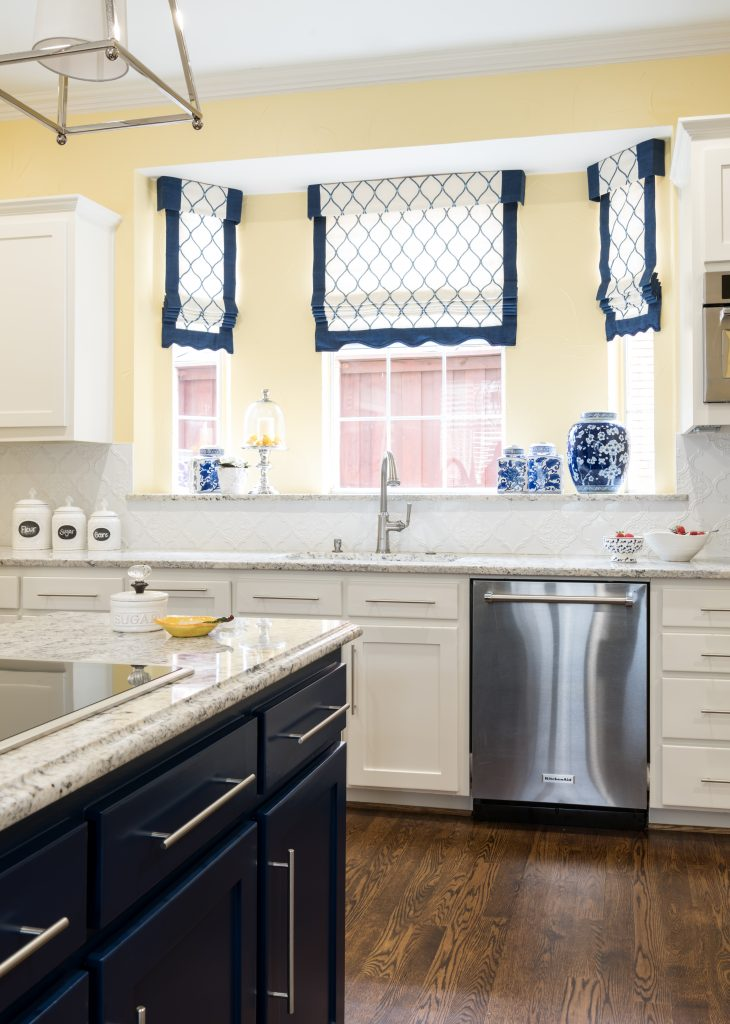 navy blue kitchen island with yellow walls with quadrefoil tile surrounded by white shaker cabinets by dallas kitchen designer dee frazier interiors