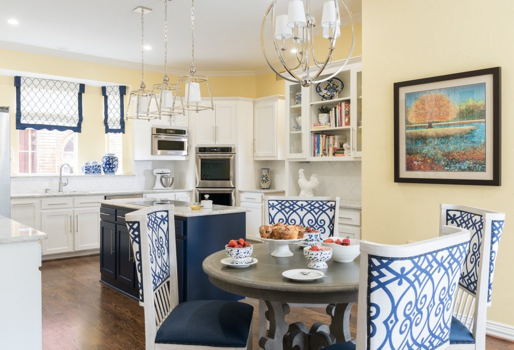 navy blue kitchen island with yellow walls surrounded by white shaker cabinets by dallas kitchen designer dee frazier interiors