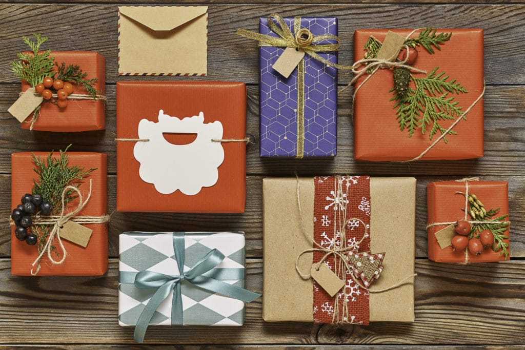 101 Holiday Gift Wrapping Ideas To Make Your Christmas Bright - A stack of flyers on a table - Christmas ornament