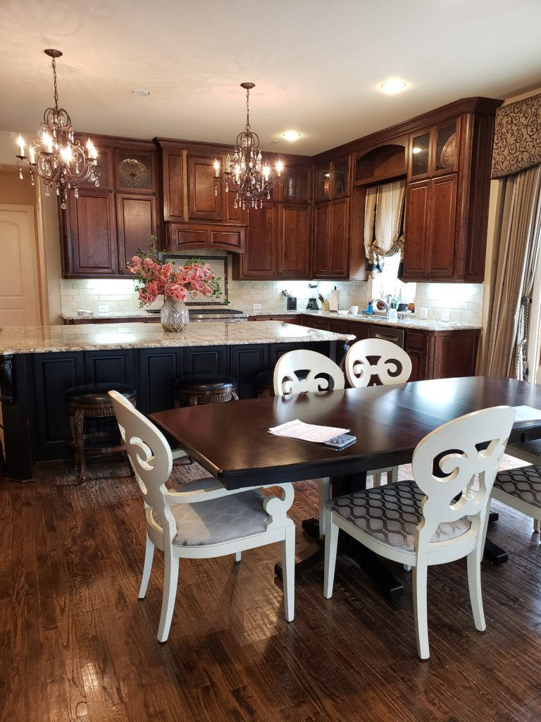 dark stained kitchen cabinets with white dining room furniture
